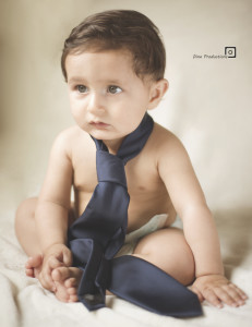 baby with dippers and blue eyes wearing blue tie